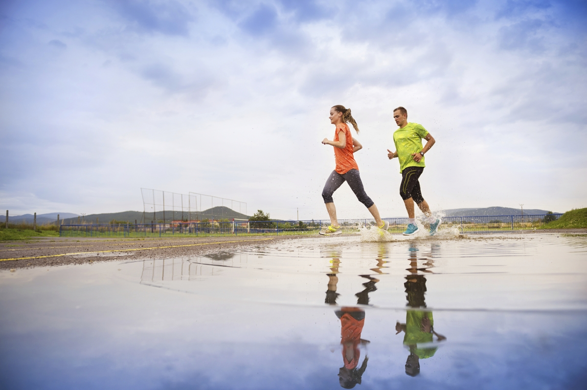 Young couple running on asphalt in rainy weather splashing in puddles.