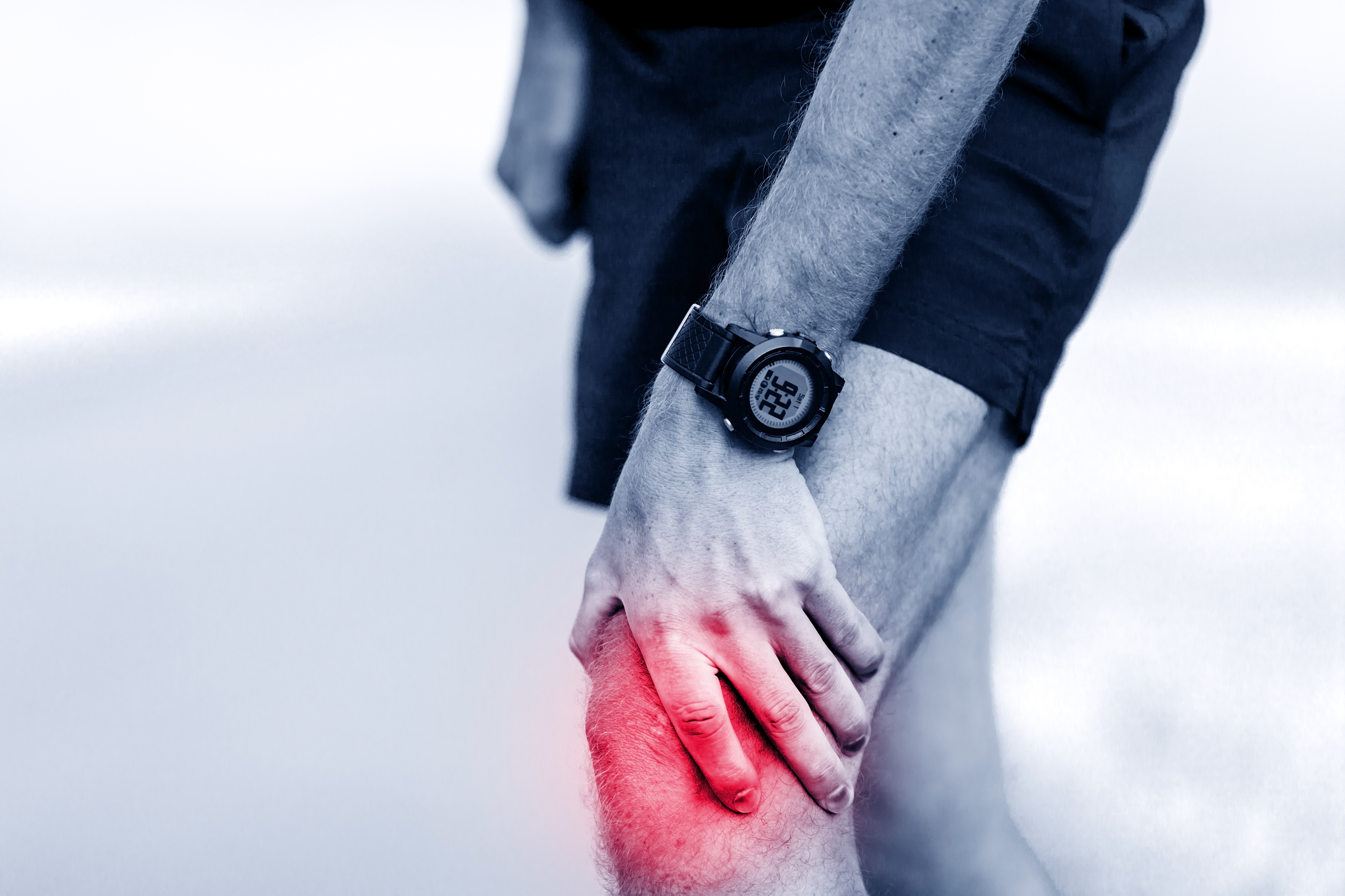 Knee pain runner leg and muscle pain running and training outdoors sport and jogging physical injuries when working out. Male athlete holding painful leg.